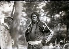 Newel Sabattus, a Passamaquoddy Indian, at the 1920 centennial of Maine Statehood in Portland. He is talking to Sabattus Mitchell. Passamaquoddy and Penobscot Indians set up a village at Deering Oaks Park for the duration of the festivities. Item # 23418 on Maine Memory Network