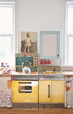 "An eclectic family home in Springfield, MO: ""The play kitchen was found on Craigslist. It is vintage and a lot of my friends have said they grew up with one just like it. We found old cheap doors at Salvation Army and cut them in half lengthwise to make the ""countertops"". The whole operation has worked out very well for storing all the kids' toys. That's Fred you see over the play stove."" #sneakpeek"