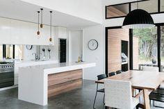 crédence adhésive en miroirs d'une cuisine en bois et blanc, table à manger en bois massif, sol en béton ciré et suspensions en métal noir
