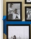 use tape to mark a mid-line, hang photo's above and below... makes a nice display of various sized frames