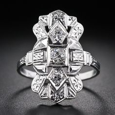 A very bright, charming and affordable original Art Deco dinner ring - circa 1930s. At arm's length, the three-quarter inch-plus long bauble appears to contain more diamonds than just the three sparklers in the center. However, a clever and talented jeweler of yesteryear created 'bright-cut' flowers where tiny diamonds would normally be set. 14 karat white gold.