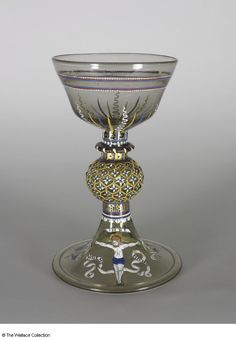 Goblet ... France (façon de Venise) mid-16th century .... Colourless glass with pinkish-grey tinge; mould-blown, applied and tooled features; enamelled in white, ochre, cornflower blue, olive green, brownish-red, black and brown, with red details; gilding. .... Height: 22.4 cm;  Diameter: 14 cm;  Inscription: 'INRI';  Inscription: 'SINE ME NICHIL'