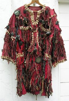 Africa | A Shaman's robe from the Senufo people of Burkina Faso | 20th century | Red cotton, cowrie shells, wool, leather encased bird skulls, leather encased amulets, and mirrors