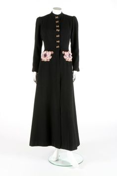 A fine and rare Elsa Schiaparelli embroidered coat, Zodiac collection, Autumn-Winter, 1938-39. Paris of black wool, the pink velvet rococo inspired pockets with Lesage embroidered gilt metal strips, the centre with violet sequined female profiles edged in gilt strip, and sprigged with gold lustre edged Sevres porcelain flowers -  http://kerrytaylorauctions.com/one-item/?id=81&sub=%20&auctionid=411#sthash.uLu7kS3w.dpuf
