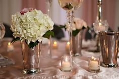 Silver mint julep vases with hydrangea and roses. Cyliander cotive holders with candles for added sparkle