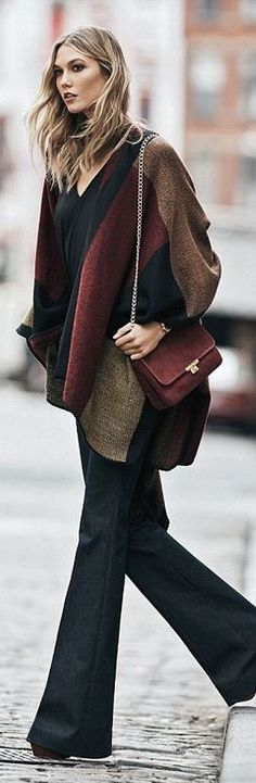 Who made Karlie Kloss' blue flared jeans, print cardigan sweater, and red handbag?