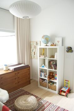 nursery with white walls, white bookcase, colorful rug
