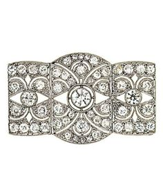 An early 20th century diamond brooch  The shaped plaque pierced and millegrain-set with old brilliant-cut diamonds, 3.9cm wide