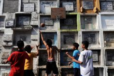 Boys played basketball next to a mausoleum at the municipal cemetery of Navotas, Philippines, north of Manila on Oct. 29.   Ezra Acayan/Zuma Press