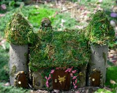 A little story book scene from the fairy garden featuring two little handcrafted castle towers and a miniature fairy cottage.