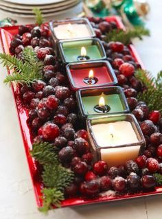Place five votive candles in a line down a red rectangular serving dish. Fill the rest of the dish with cranberries.