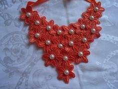Maxi colar com flores de renda laranja com botoões de chatons de perola clara. Fecho em fita de cetim laranja R$35,90