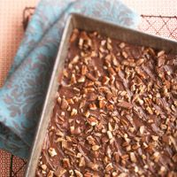 A brown sugar cookie layer gets topped with melted chocolate and sprinkled with walnuts and toffee candy.