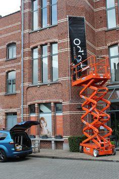 Plaatsing tegen gevel van een buizenframe met spandoek voor Odisee hogeschool te Schaarbeek.