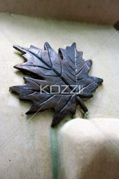 Metal Maple Leaf - A metal maple leaf on a white surface.