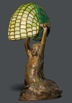"""TIFFANY STUDIOS N.Y.<br><br> """"Nautilus/Mermaid"""" TABLE LAMP, circa 1910<br>Favrile glass and bronze with a brown patina.<br>The base stamped Tiffany Studios New York, 28631, CLT CO. H. 40 cm.<br><br><br> --------------- <br>TIFFANY STUDIOS N.Y.<br><br>TISCHLAMPE """"Nautilus/Mermaid"""", um 1910<br>Favrile Glas und Bronze braun patiniert. Meerjungfrau mit grünem Schirm in Form einer Nautilusmuschel.<br>Boden gestempelt Tiffany Studios New York, 28631, CLT CO. H. 40 cm.<br><br>"""