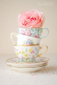Rose topper on stack of china tea cups.