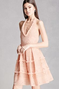 A halter dress featuring an ornate crochet design, fringed trim, a ribbon halter self-tie, tiered skirt, and an exposed back zipper.