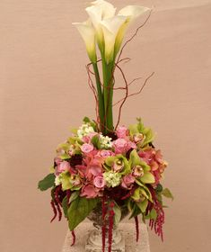 """A Topiary Decadence""  A Topiary of Calla Lilies surrounded by a bed of exquisite Cymbidium Orchids, Hydrangeas, Roses, Roses, and Bells of Ireland, dripping with flowing Red Hanging Amaranthas, and laced with Curly Willow branches to create a spectacle of some of the most gorgeous flowers available! Simply Stunning!"