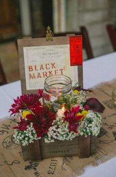 Sweet flowers in a cigar box and a candle for a fall wedding