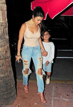 Hold on tight: The mother-of-three looked every inch the yummy mummy as she teamed a plunging nude bodysuit with extremely ripped jeans