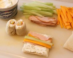 """""""Sushi"""" sandwiches for kids.  Directions    1.Slice the cheddar cheese and cucumber into long thin pieces.  2.Cut the crusts off the bread.  3.Roll the cheese, cucumbers, cream cheese and turkey up in a piece of white bread. I also added mustard to some.  4.Slice the roll in half. Slicing with a knife helps make the roll stick.  5.Place on a plate like real sushi and watch your guests eat them up!"""
