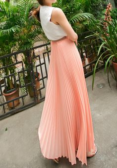 Right side view of model in pink pleated maxi skirt and white top