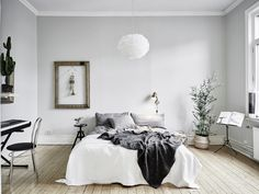 Black, white, and gray bedroom with cozy bed, trumpet framed on the wall and indoor plant