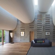 The swooping ceiling of this house in Japan is designed to improve acoustics inside a living room that is also used for music recitals.