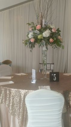 Floor to ceiling draping, ruched chair covers, champagne sequin overlays, full length champagne satin tablecloth, tall floral centerpiece.  #920events #920eventsdecor #sterlinggardensneenah #breathtaking #weddingshow #wedding #ideas