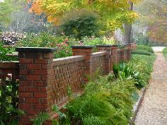 Brick wall enclosing a garden at Fall. A bench inside the garden wall with custom rod iron legs.