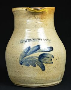"Price Realized: $ 1,207.50    Cobalt-Decorated Stoneware Pitcher, Stamped ""COWDEN & WILCOX,"" Harrisburg, PA origin, circa 1865, ovoid-waisted pitcher with tall, slightly-flared collar, decorated with a brushed cobalt tulip extending from a leafy stem. Excellent, as-made condition with an in-the-firing separation on underside of upper handle terminal, and a small stone ping to rim. H 8 1/4""."