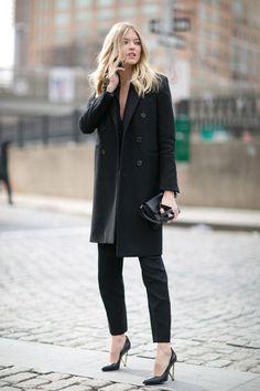 Марта Хант в черных брюках и пальто прямого кроя, черный клатч