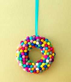Super simple wreath idea using craft pom-poms.  Customize it for the holiday of your choice by choosing specific colors.
