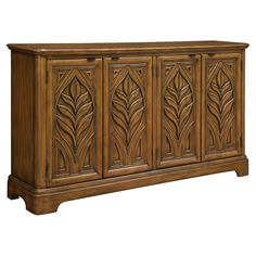 Featuring carved panels with a nature-inspire motif, this 4-door sideboard is perfect for stowing spare throws in the den or dinnerware in the kitchen.