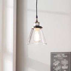 This clear glass pendant showcases a bowed shape and bronzed metal accents for a striking look overhead.