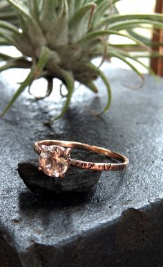 This ring has a 14 karat band with .4 carat round morganite stone. The setting has a line textured inner ring with contrasting shiny prongs holding the stone. The rose gold bring out the pink of the m