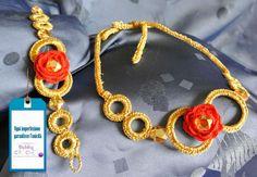 """Parure composta da collana e bracciale in filo di cotone dorato. Di questa creazione sono particolarmente orgogliosa. Sia la collana che il bracciale presentano anelli concentrici di due misure differenti nel cui centro è posta, a contrasto, una rosellina rossa. Il piccolo fiore rosso ha al suo centro la """"solita"""" perla sfaccettata che illumina il manufatto. La parure può essere richiesta, secondo i vostri gusti, in tinte differenti o acquistata singolarmente."""