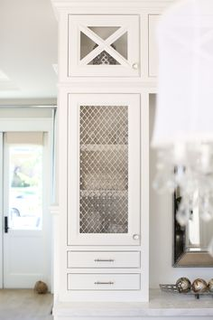 The cabinet, painted in a soft white, features x mullion, glass knobs and Wire Mesh Grilles. Wire Mesh Grilles Patterson Custom Homes. Interiors by Trish Steele, Churchill Design. Coastal Furniture, Coastal Decor, Modern Coastal, Coastal Industrial, Coastal Curtains, Coastal Entryway, Coastal Rugs, Coastal Farmhouse, Coastal Cottage