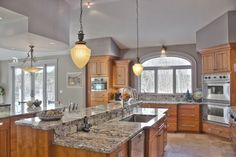 Transitional Kitchen- Counter height seating, Stainless Steel appliances, built in corner ovens, pantry pull-outs flanking the refrigerator, Multi tier countertop as well as custom soffit design, natural cherry cabinets, granite countertops