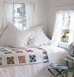 A COLORFUL QUILT stands out in this mostly white room.  This looks like a lovely, comfortable and breezy place to rest and relax!