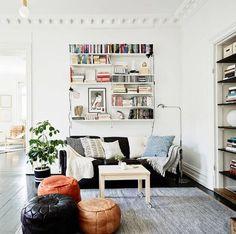 decoração de sala de estar com puffs de couro em várias cores, sofá preto com aprateleiras formando uma estante em cima do sofá