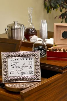 Consider something totally different from the traditional wedding reception bar. Create a late night bourbon and cigar wedding bar. Use an antique furniture piece or a piano as the stage for a small selection of top-shelf bourbon whiskey, a bucket of ice, custom printed plastic tumbler cups, a humidor full of cigars, cigar cutter and a basket or bowl of personalized matchbooks. What a perfect setting for a Gatsby or gangster theme wedding.