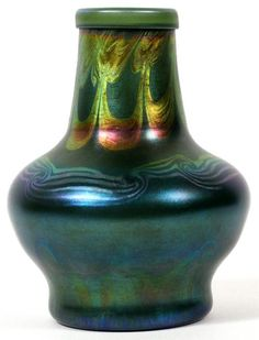 """Found on EstateSales.NET: Lot#1061,L. C. TIFFANY BLUE FAVRILE GLASS VASE, C. 1900, H 7 1/4"""", DIA 5 1/2""""Blue Favrile glass with pulled scroll motif about the neck, shoulder and base.  Signed """"LCT M 7138"""" (see additional photo)."""