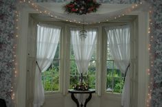 Interior. triple white sheer Bay Window Curtains with black back tiecord  and glass window on white wooden frame also hanging small lamp on floral pattern white wallpaper. Beautiful Decoration Of Bay Window Curtains Brings Awesome Looks