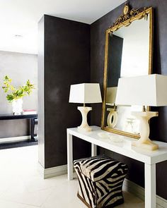 The dark gray wall looks so dramatic with the gold mirror and white table and lamps.