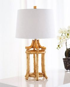Handcrafted chinoiserie table lamp inspired by a vintage bamboo lantern. Cast-resin, open bamboo lantern-style frame. Hand-applied gold-leaf finish. Silk/polyester blend shade with golden lining. Thre