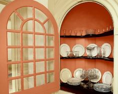 The interior of a beaufet in the 1719 St. George Tucker House in Colonial Williamsburg is painted shocking citrus—Pratt & Lambert's Tucker Cupboard Orange CW105—all the better to show off antique plates displayed on curvaceous black shelves.    A beau´fet is a niche or cupboard specifically to hold dinnerware, silver and other vessels.