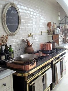 White tile kitchen with antique stove & pot filler. . Beautiful