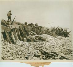 Des soldats américains se tiennent sur des galets devant un muret, probablement à Dog White, vers le 7 juin 1944. Des obstacles de plage : h...